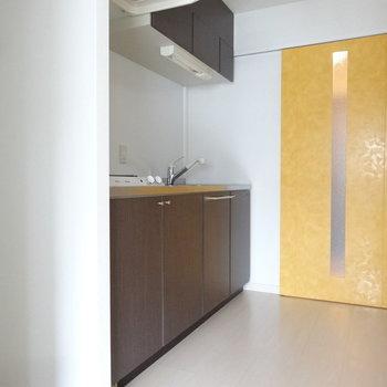 キッチンスペース。黄色の引き戸がアクセント。※写真は別室です。