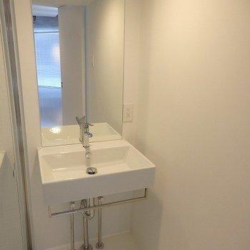 ガラス張りのお風呂の隣に洗面台。※写真は2階の同間取り別部屋です