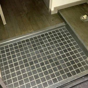 玄関は小さめ。洗濯パンの上に靴箱あり(写真は清掃前です。フラッシュ撮影しています。)
