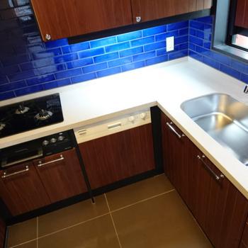 L型のキッチン。使いやすそうですし青いタイルがカッコイイ!