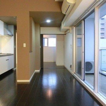 ブラウン系で落ち着いた印象のリビングスペース(※写真は8階の同間取り別部屋のものです)