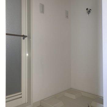 洗面台の前に洗濯機置き場があります※写真は通電前・フラッシュを使用して撮影しています