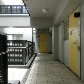 共用部。黄色いドアが印象的。※写真は5階の別間取り別部屋です