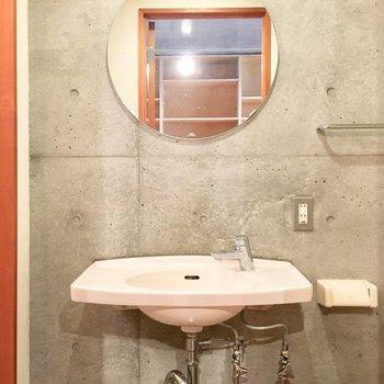 洗面台も丸い鏡もシンプルでおシャレ。