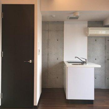 打ちっ放しの壁とキッチンも。※写真は7階の反転間取り別部屋です。