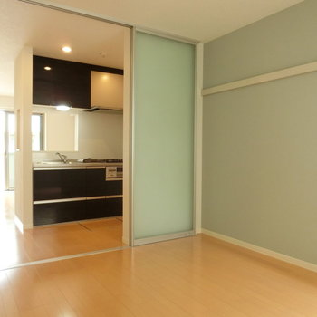 エメラルドグリーンの壁とパーテーション。キッチンとLDKを眺める