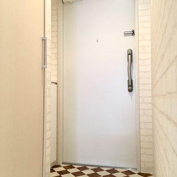 玄関はハーリキン柄がアクセントに。(※写真は2階の同間取り別部屋のものです)