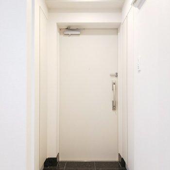 玄関は黒の床で引き締まった印象に。