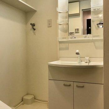 独立洗面とその横に洗濯機置場。※写真はクリーニング前の物です。
