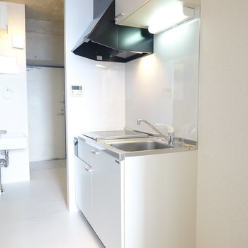 部屋に馴染む白のキッチン。周りのスペースもちょっと広いので調理台用のワゴンも置けそう。