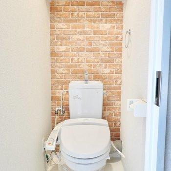 レンガ調クロスのあるウォシュレット付きトイレ。遊び心が凄い。