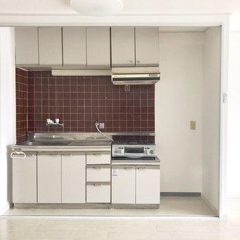 キッチンの赤いタイルが素敵。※写真は電気がつく前のものです。