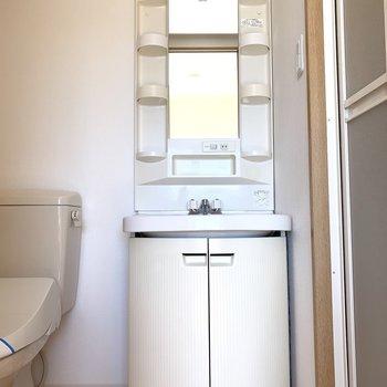 ドアを開けると洗面化粧台とトイレ。(※写真は14階の反転間取り別部屋のものです)