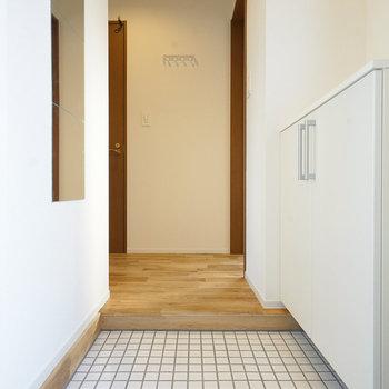 玄関は白タイルに下駄箱を新設!※写真は同間取り同階、別部屋のものです。