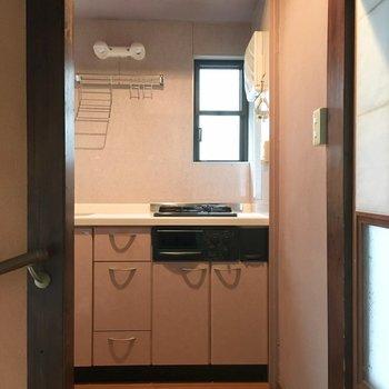 玄関を入って左側にキッチン。扉がないのでのれんをかけて。