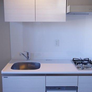 白いシステムキッチン※写真は6階の反転間取り別部屋のものです。
