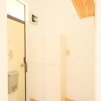 玄関前には靴箱、棚、コート掛けが。充実してます。※写真はクリーニング前、前回募集時のものです