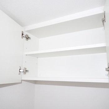 トイレ上部にはペーパー置き場。(※写真は15階の反転間取り別部屋・通電前のものです。)