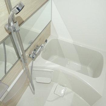 バスルームも木調!シャワーヘッドは大きめです。(※写真は15階の反転間取り別部屋・通電前のものです。)