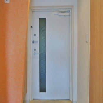 玄関のオレンジ壁で明るく