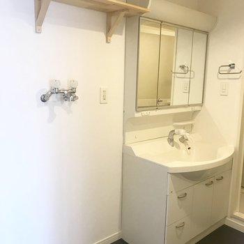 大きな洗面台の横には無垢の棚