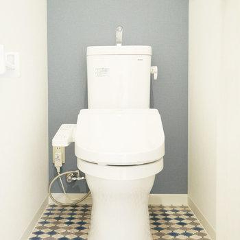 くすんだトイレはブルーのクロスとタイル調の床がかわいい