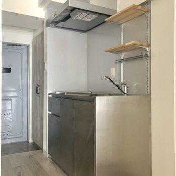ステンレスのキッチン。調味料棚がおしゃれに見えます。※写真は電気がつく前のものです。