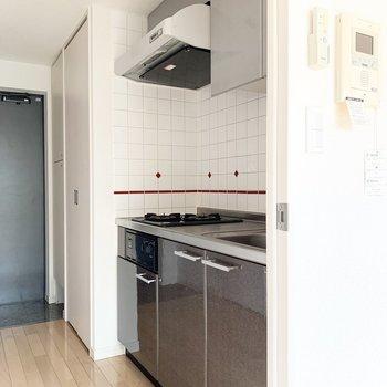 グレーのキッチンと赤いタイルが素敵です。