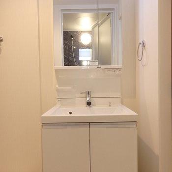 独立洗面台の横に洗濯機。※写真は別部屋です