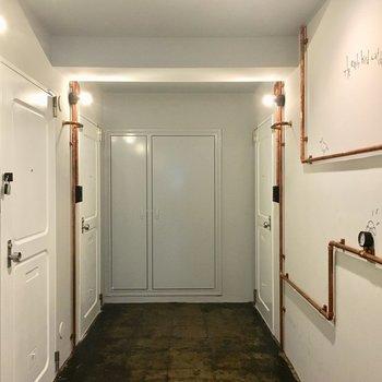 白いドアを取り囲む銅のパイプ