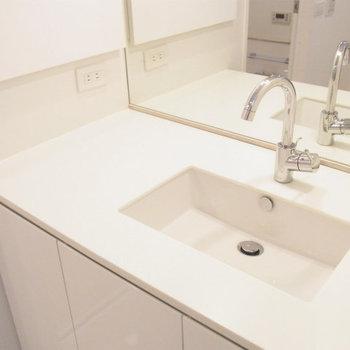 洗面台もシンプル。奥には大容量の収納も。※写真は6階の同間取り別部屋です。