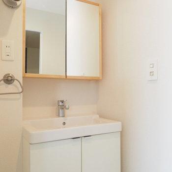 洗面台はオリジナルデザイン、木枠の鏡は収納に。