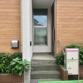 少し高くなった所に玄関ドア。ゴミ置き場があるけど蓋つきできれいです。