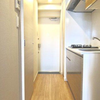 居室ドアを開けるとキッチンと水回り。※写真は6階の同間取り別部屋のものです。