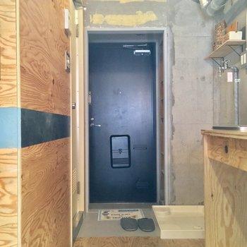 玄関はキッチン奥に。洗濯機置場もコチラに
