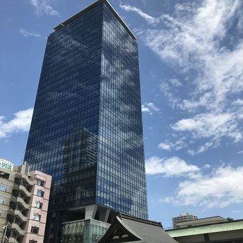 青空が映る高層ビルと日本建築
