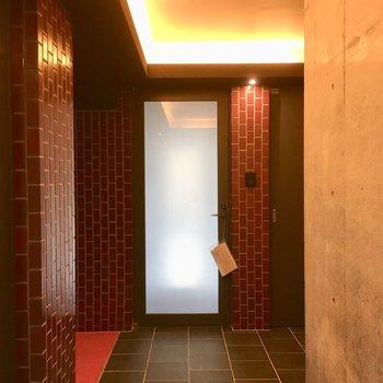 朱色のレンガ、透明の玄関ドアが並ぶ美しい共用部。