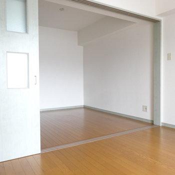 洋室から見るとこんなかんじ。引き戸もキッチンと同じグリーンで。(※写真は9階の反転間取りの別部屋のものです)