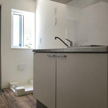 キッチン横に冷蔵庫置き場・洗濯機置き場があります。※クリーニング・電気がつく前の写真