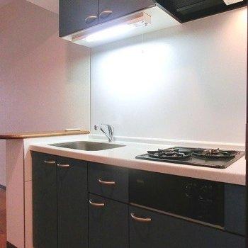 カウンター付きの2口ブルーのキッチン※写真は同間取り別部屋のものです。