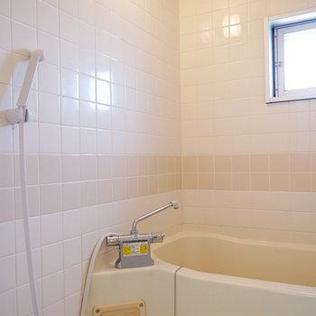 浴室の壁はベージュのタイル。窓ありで明るい
