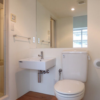 洗面台と大きな鏡、トイレも隣に※写真は同間取り別部屋のものです