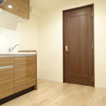 キッチンエリアはナチュラルブラウン。※写真は同間取り別室です。