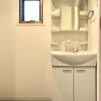 洗面台はスタンダードなタイプ。脱衣所には小窓が付いているし、細長い収納ケースなら置けそう!(※写真は8階の反転間取り清掃前のお部屋のものです)