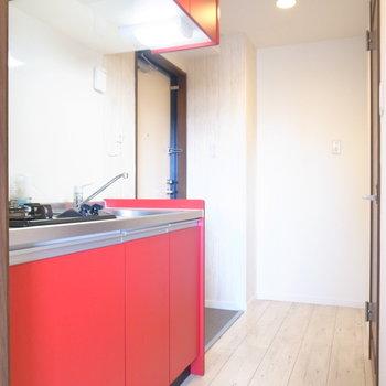 キッチンは大人っぽいレッドカラー!冷蔵庫は廊下の突き当たりに置きましょう。