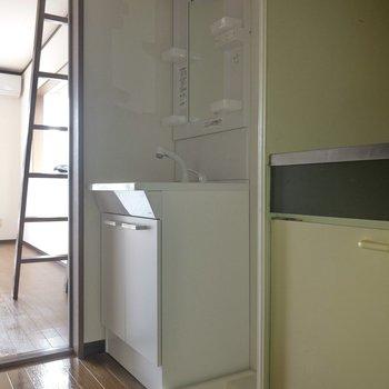 洗面台は廊下に。その隣には洗濯機置き場が。