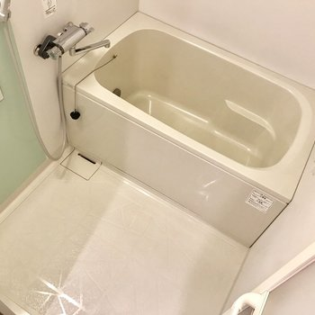 洗面台のお隣にお風呂。ミントグリーンの壁がチラリ。