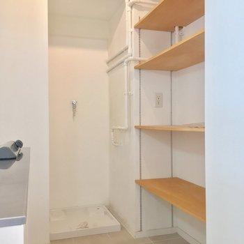 キッチン背面には便利な収納棚。洗濯機置場も奥にチラリ