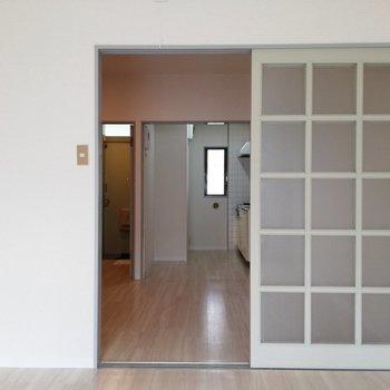 洋室の扉を開けると、キッチンが見えます※写真は2階の同間取り別部屋のものです