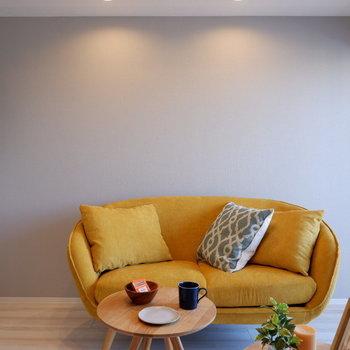 黄色いソファとアクセントクロスのグレーが合う!※写真は7階の反転間取り別部屋のものです